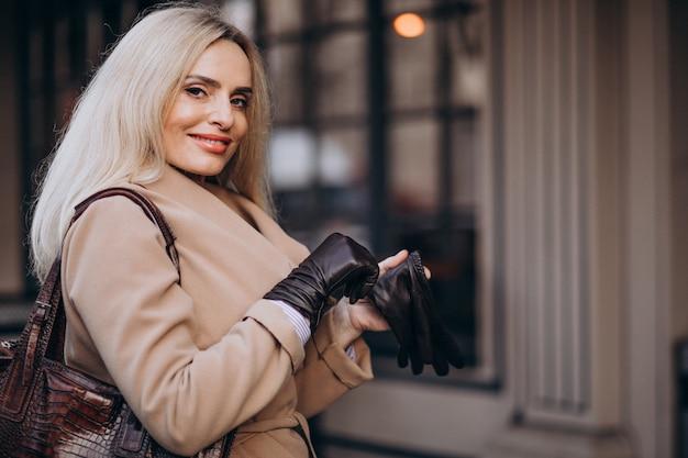 Personnes âgées Femme D'affaires Dans Un Manteau Avec Des Gants Dans La Rue Photo gratuit