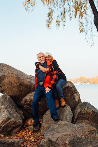 Personnes âgées Gaies Une Femme Et Un Homme Sont Assis Sur Les Pierres Et S'étreignent Sur Le Lac Photo Premium