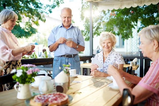 Personnes âgées jouant aux cartes au café Photo gratuit