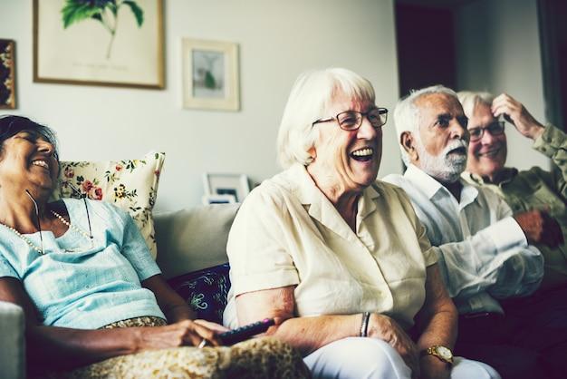 Personnes âgées regardant la télévision dans le salon Photo Premium