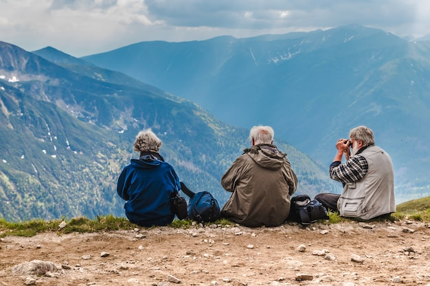 Les Personnes âgées Avec Des Sacs à Dos Sont Assis Sur Le Sol Haut Dans Les Montagnes Photo Premium