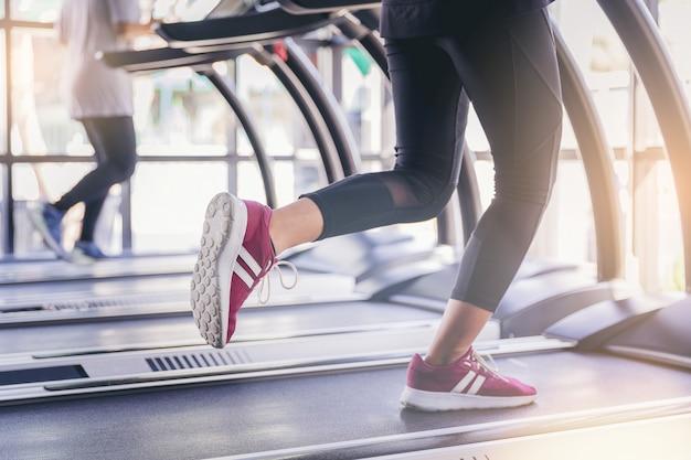 Personnes en cours d'exécution dans le tapis roulant de la machine à la salle de fitness Photo Premium