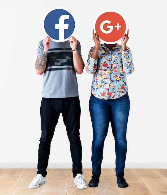 Personnes détenant deux icônes de médias sociaux Photo gratuit