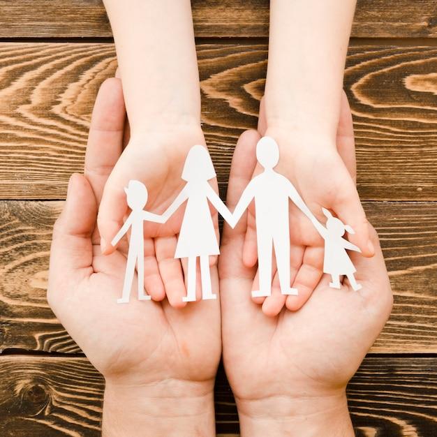 Personnes Détenant Une Famille De Papier Sur Fond De Bois Photo gratuit
