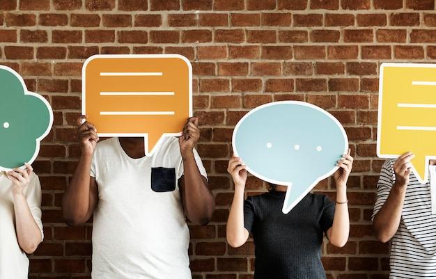 Personnes détenant des icônes de bulle de dialogue Photo Premium