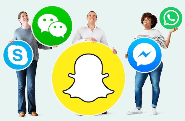 Personnes détenant des icônes de marques numériques Photo gratuit