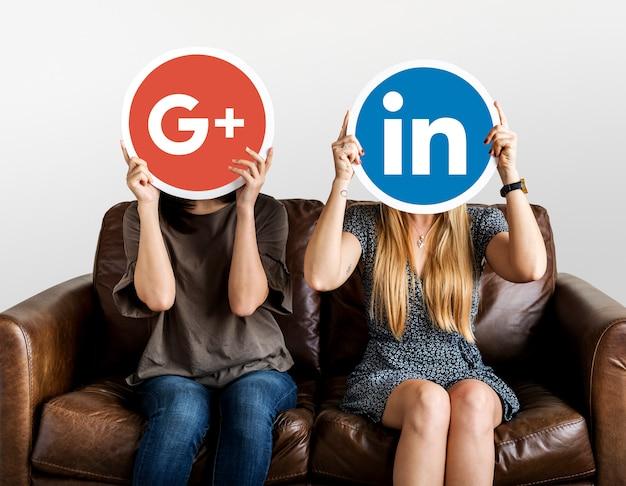 Personnes détenant des icônes de médias sociaux Photo gratuit