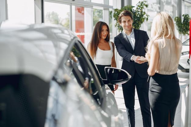 Personnes élégantes et élégantes dans un salon de l'automobile Photo gratuit