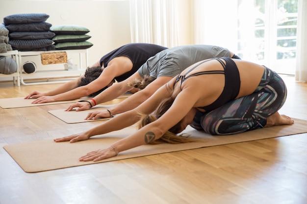 Personnes faisant l'enfant posent sur des nattes au cours de yoga Photo gratuit