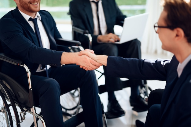 Les personnes handicapées en costume d'affaires dans une salle lumineuse. Photo Premium