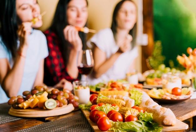 Personnes mangeant des apéritifs arrière-plan flou Photo gratuit