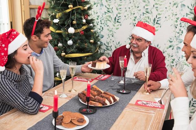 Personnes mangeant des bonbons à la table de fête Photo gratuit