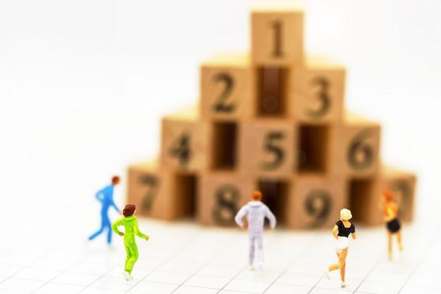 Personnes miniatures en cours d'exécution devant le numéro de la boîte en bois. Photo Premium