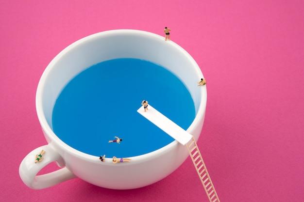 Personnes Miniatures Dans La Tasse Tasse Piscine Photo Premium