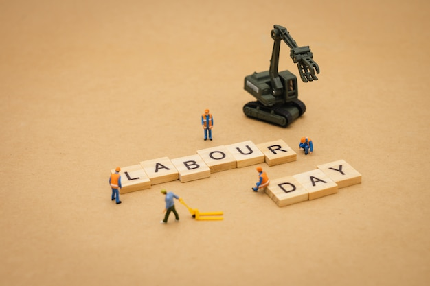 Personnes miniatures debout avec le mot bois fête du travail utilisant comme arrière-plan journée universelle Photo Premium
