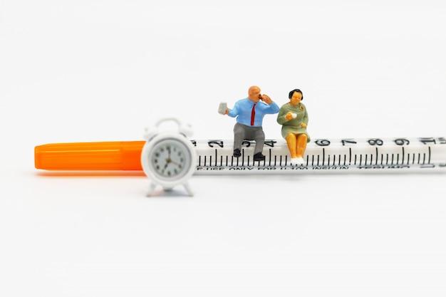 Personnes miniatures: gros patients assis sur une seringue et une horloge. concept de soins de santé. Photo Premium