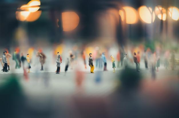 Les personnes miniatures marchant dans les rues, les gens se déplacent à travers le passage piétonnier Photo Premium