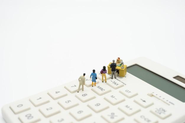 Personnes miniatures payer le revenu annuel (tax) de la file d'année sur la calculatrice. Photo Premium