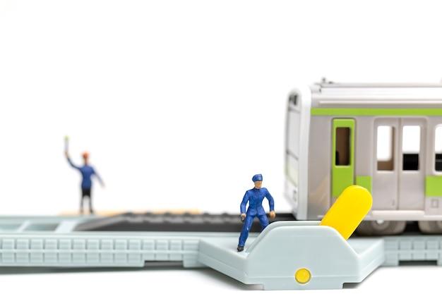 Personnes miniatures: le personnel des chemins de fer travaille au chemin de fer sur fond blanc Photo Premium