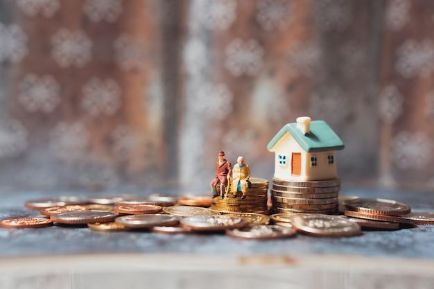 Personnes miniatures, personnes âgées assis sur des pièces de pile Photo Premium