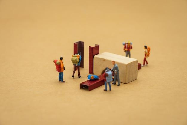 Des personnes miniatures se tiennent debout passez dans le scanner avant d'entrer dans la porte de l'aéroport. Photo Premium