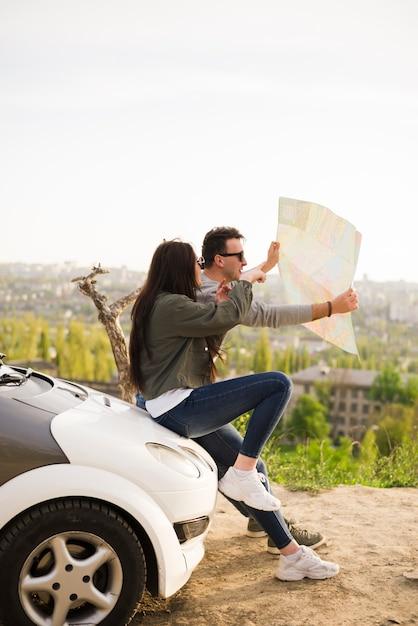 Personnes naviguant avec une carte lors d'un voyage en voiture Photo gratuit