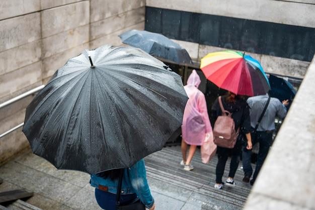 Les Personnes Avec Des Parapluies Descendent Dans Le Passage Souterrain. Paysage Urbain Un Jour De Pluie. Parapluie Avec Des Gouttes De Pluie. Mauvais Temps. Photo Premium