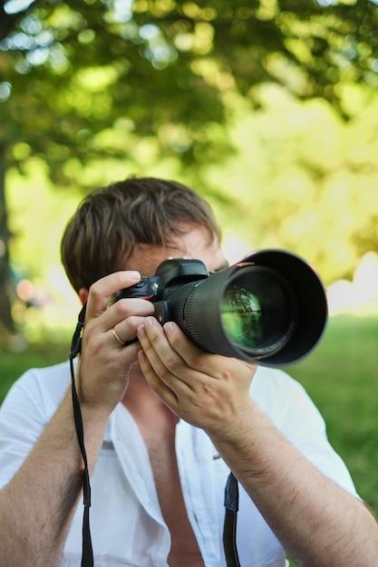 Personnes photographie technologie loisirs et style de vie hipster homme tenant un appareil photo numérique avec objectif grand Photo Premium