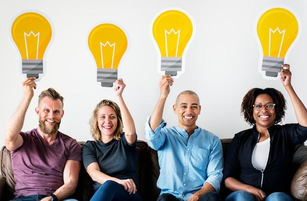 Personnes portant des icônes d'ampoule Photo gratuit