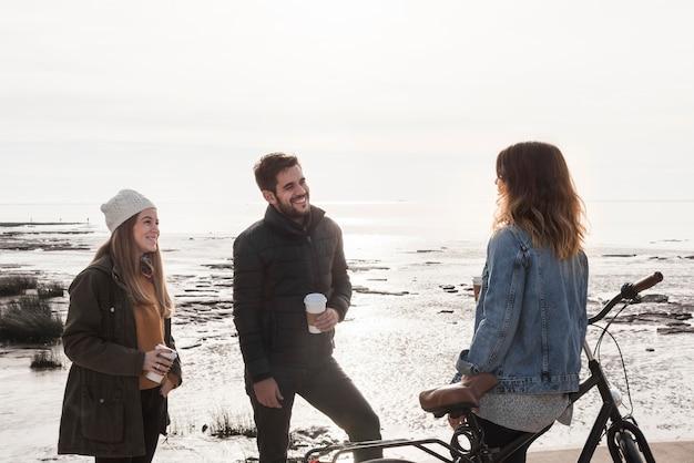 Personnes portant des vêtements chauds parlant au bord de la mer Photo gratuit