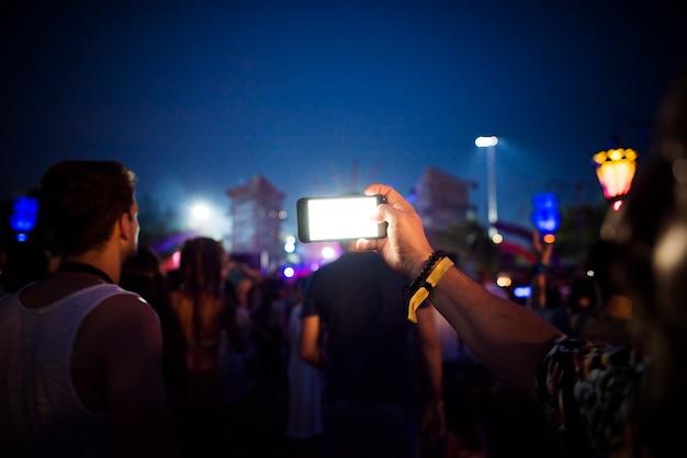 Personnes prenant des photos lors d'un festival de concerts de musique Photo gratuit
