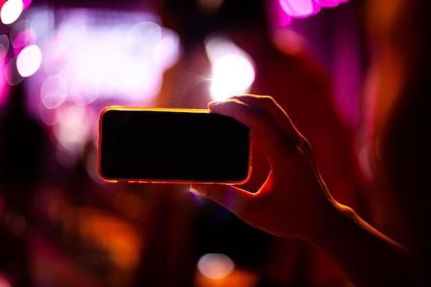 Personnes prenant des photos avec un téléphone intelligent pendant un concert de musique en direct et la foule Photo Premium