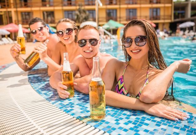 Personnes s'amusant dans la piscine en souriant et en buvant de la bière Photo Premium