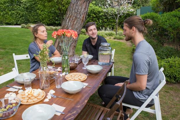 Personnes séropositives prenant son petit déjeuner à une table en bois dans la cour Photo gratuit