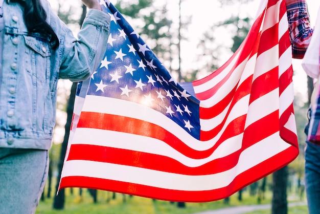Personnes tenant le drapeau des etats-unis dans le parc Photo gratuit