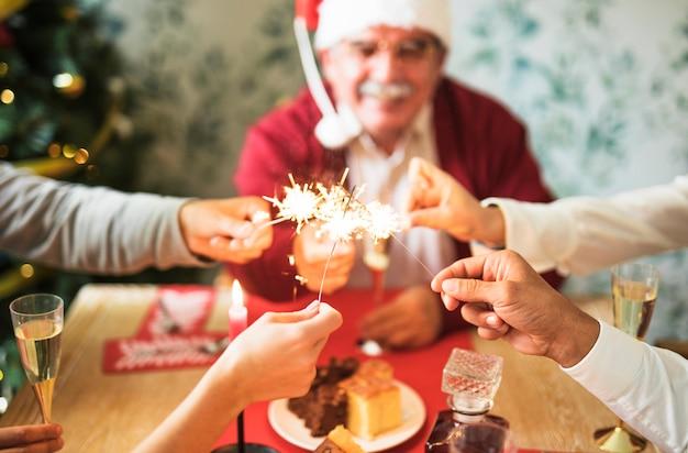 Personnes tenant des feux de bengale en feu à la table de fête Photo gratuit