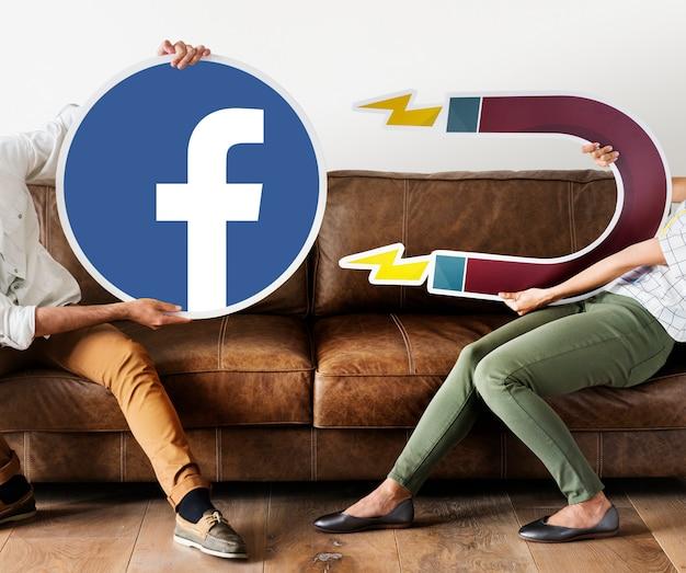 Personnes tenant une icône facebook Photo gratuit