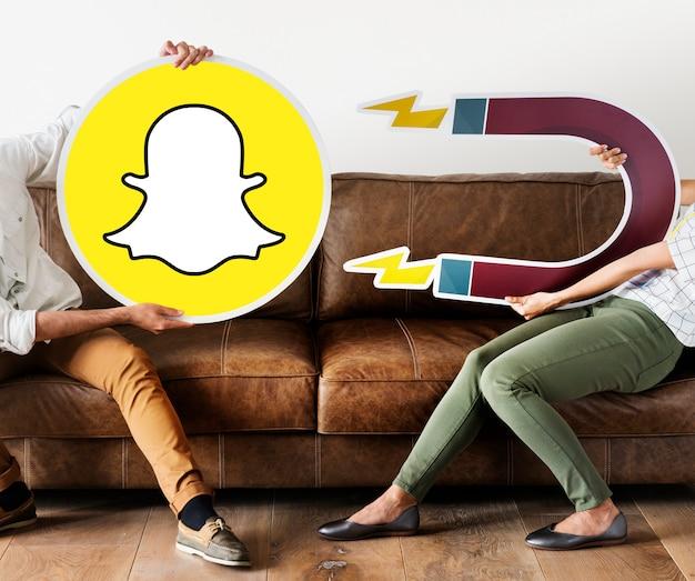 Personnes tenant une icône snapchat Photo gratuit