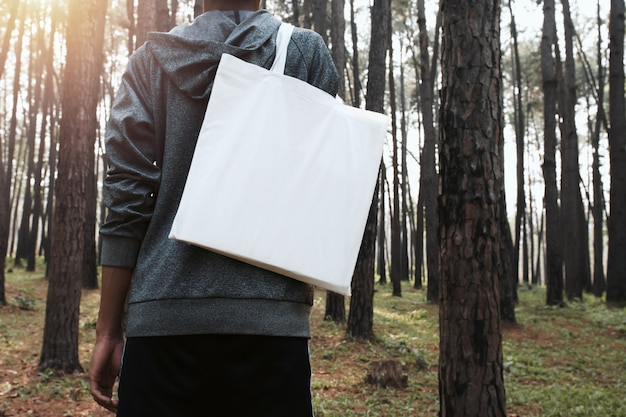 Personnes tenant un sac en coton pour maquette vierge au fond de la nature Photo Premium