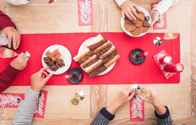 Personnes en train de manger un dessert à la table de noël Photo gratuit