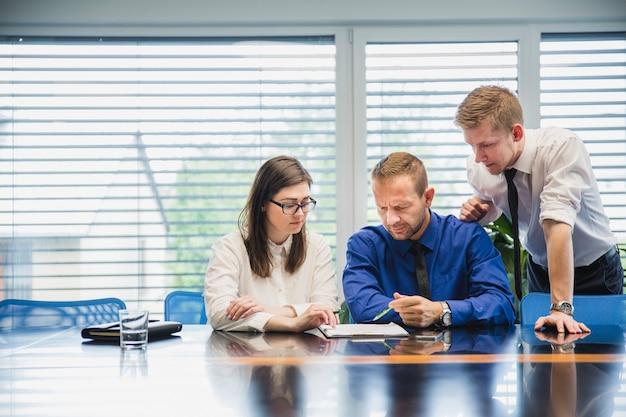 Personnes travaillant au bureau avec des papiers Photo gratuit