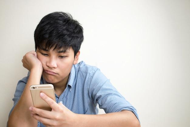 Des personnes tristes vérifient leurs courriels sur leur téléphone portable dans la chambre. Photo Premium
