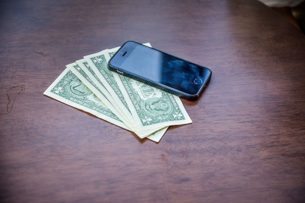 Les Personnes Utilisant Un Smartphone Pour Faire Leurs Achats En Ligne Par Internet, Smartphone Et Dollar Américain Sur Bois Pour Faire Du Shopping Ou économiser Et Investir Photo Premium