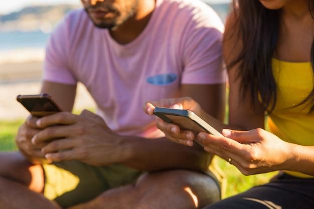 Personnes utilisant un téléphone portable dans un parc Photo gratuit