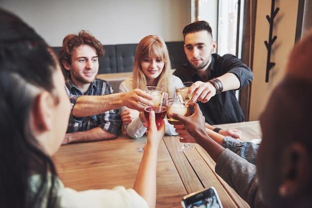 Personnes avec des verres de whisky ou de vin célébrant et grillant Photo Premium