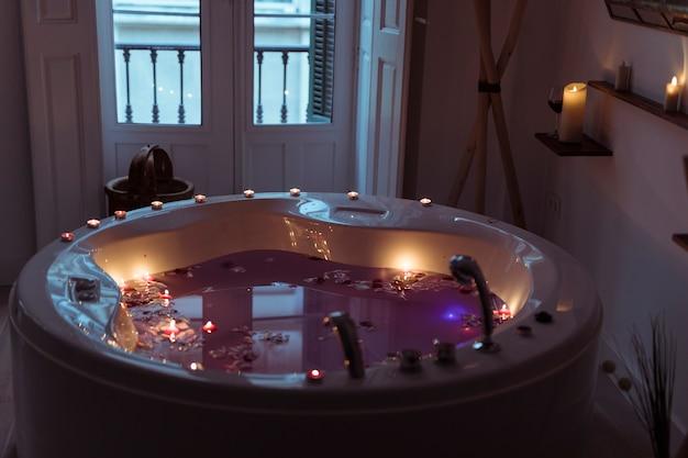 Pétales de fleurs sur l'eau dans la baignoire spa avec des bougies allumées sur les bords Photo gratuit