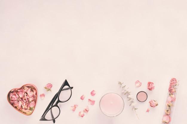 Pétales de rose avec des lunettes et des bougies sur table Photo gratuit