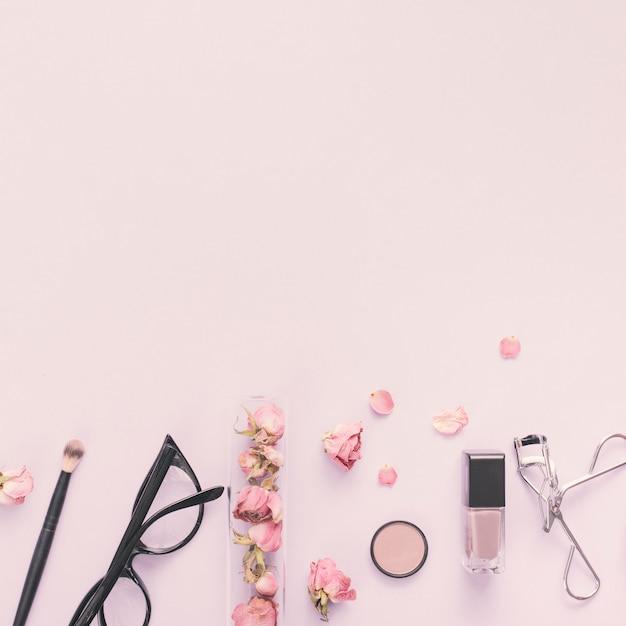 Pétales de rose avec des produits cosmétiques sur la table Photo gratuit