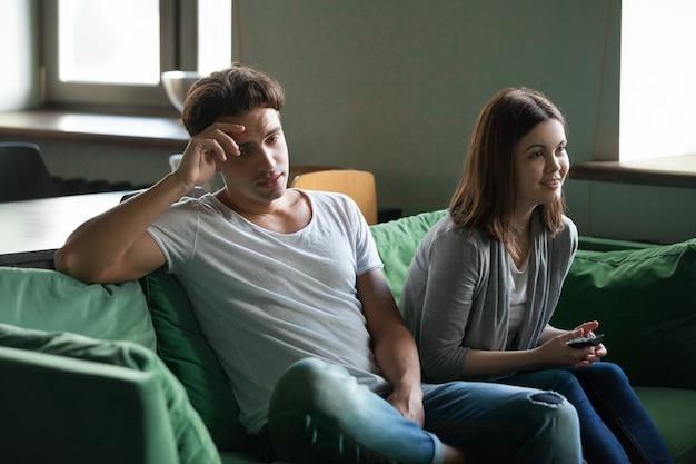 Petit ami désintéressé s'ennuie alors que sa petite amie excitée regarde une série télévisée Photo gratuit