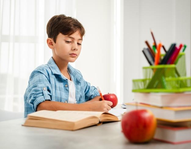 Petit Angle Garçon Mange Une Pomme Pendant Ses études Photo gratuit